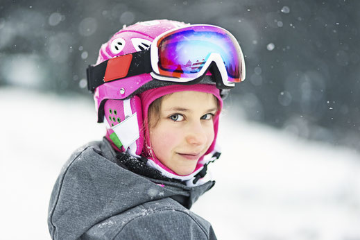 Young girl in pink ski helmet and goggles