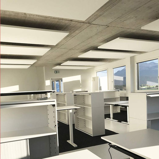 Grossraumbüro mit weissen Deckenpanelen an Betondecke als einziger Schallschutz