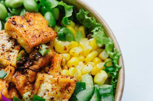 Eine bunte Bowl mit knusprigem Tofu, Mais und Salat