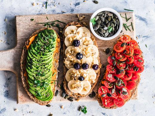 Vollkornbrote, belegt mit Hummus, Avocado, Tomaten und auch Banane und Erdnussmus