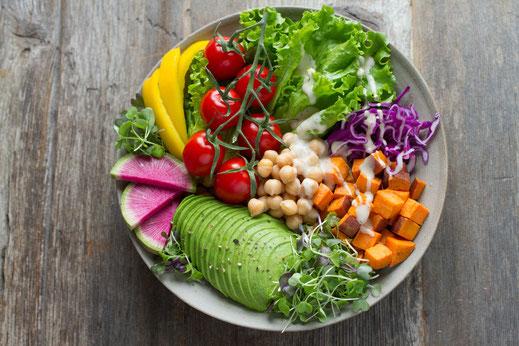 Eine bunte Bowl mit Avocado, Rohkost, Süßkartoffel und Kräutern