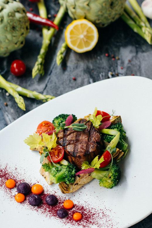 Ein gebratenes Stück Fleisch, garniert neben viel buntem Gemüse