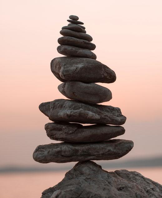 Steine von groß nach klein aufeinandergestapelt und in Balance gebracht