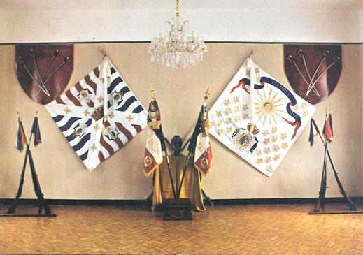 Vue des drapeaux et fanions de la Salle d'Honneur du 99e R.I. (bâtiment PC). Entre les emblèmes, l'urne contenant les cendres du drapeau brûlé en 1940