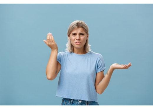 Schlagfertigkeit: Frau steht ratlos mit erhobenen Armen vor einem blauen Hintergrund