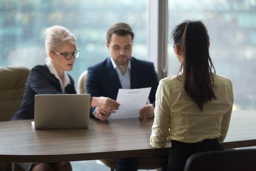 Vorstellungsgespräch: Frau sitzt mit zwei Personen am Tisch