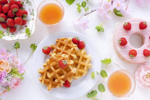 春のティータイム。イチゴが盛りつけられた器。ワッフル。イチゴチョコのバームクーヘン。