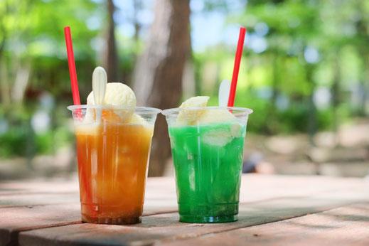 オフィスのフリースペースのテーブルでコーヒーを飲みながら、スマートフォンを覗き込み談笑する女性3人。