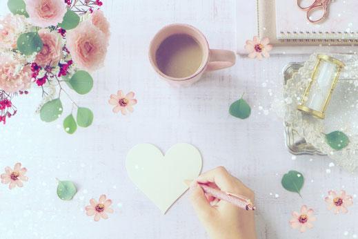 ハート形のメッセージカードに書き込もうとするボールペンを握った手。バラの花のブーケ。コーヒーの入ったマグカップ。積まれたノート。