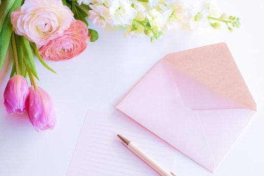 ピンクの封筒とボールペン。ピンクのバラとチューリップの花束。