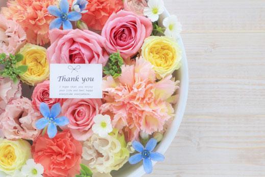 ピンクとイエローのバラとカーネーションのアレンジメント。「ありがとう」のメッセージカード付き。