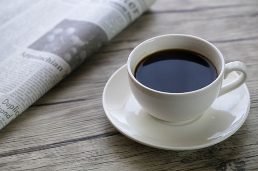 木製テーブルのうえに置かれた英字新聞とコーヒーの入ったカップ&ソーサ。