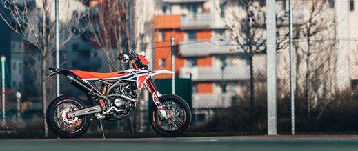 Fantic XMF 125 Competition rechte Seitenansicht vor Zaun
