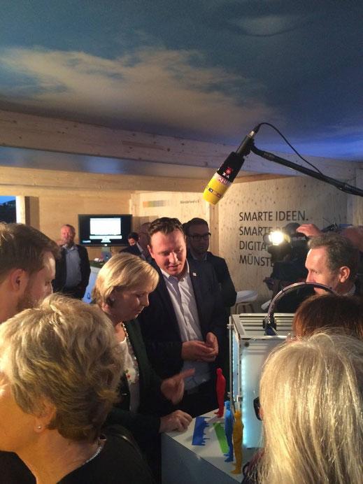 Juri Boos und Max Tönnemann erklären Hannelore Kraft in Berlin einen 3D-Drucker