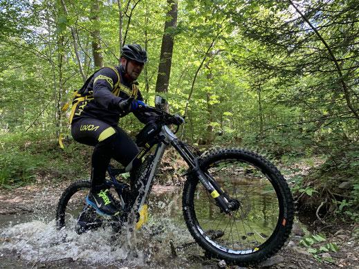 E-Biker fährt durch einen Fluss auf Tour mit dem Harzer E-Bike Verleih