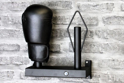 black boxing glove dryer mounted on a grey brickwall, a single black boxing glove is fitted