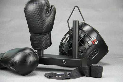 black boxing glove dryer with boxing gloves and a helmet , grey background