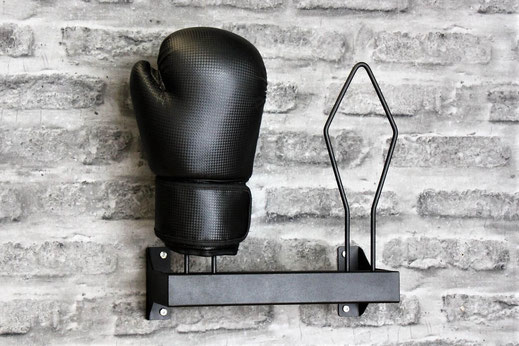 back boxing glove rack mounted on a grey brick wall, a black  boxing glove is fitted