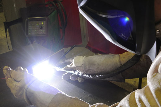 A welder is welding steel casings with TIG on a table