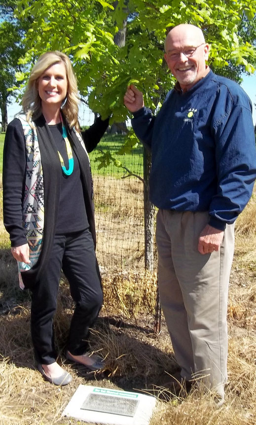 Megan Pierce, Program Assistant (left), with David King, Executive Director PLC, standing near the tree donated by  PLC in the Rezab Family Prairie Meadow.
