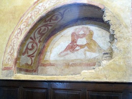 """Sur le tympan du portail muré, le combat d'un homme contre un ange, """"un combat qui pourrait être celui de Jacob contre l'ange envoyé de Dieu, ou Dieu lui-même manifesté sous une forme visible"""" (abbé Porée)."""
