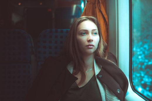 Hübsche junge Frau unterwegs im Zug in Liebeskummer