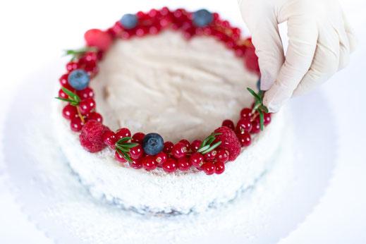 Dekorieren der Torte mit verschiedenen roten Früchten und Blaubeeren