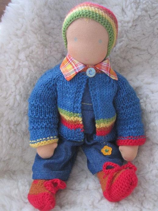 Puppenjunge Matze trägt nun eine hübsche Regenbogen-Strickjacke mit niedlichem Vogelknopf und passender Mütze und Schühchen (das blaue Garn ist pflanzengefärbt, alles ist reine Schurwolle)