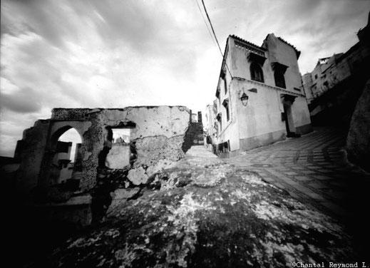 une rue, un porche, un mur délabré et des maisons tout cela en noir et blanc