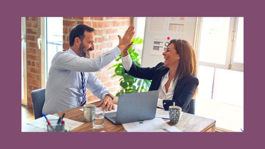 Mann und Frau klatschen sich ab bei der Büroarbeit