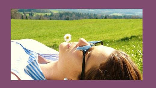 Frau entspannt im Gras liegend