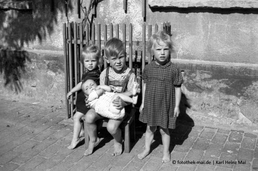 Zwei Kinder auf Stuhl mit Baby und Mädchen stehend auf dem Hof, alle barfuß