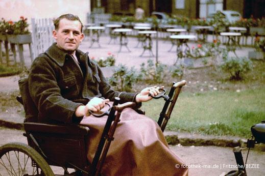 Fotograf Karl Heinz Mai, Deutschland, im Rollstuhl um 1952 in Leipzig. Farbfoto.