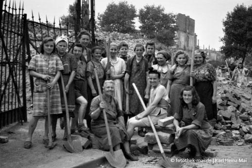 Trümmerfrauen vor Ruine und Gittertor
