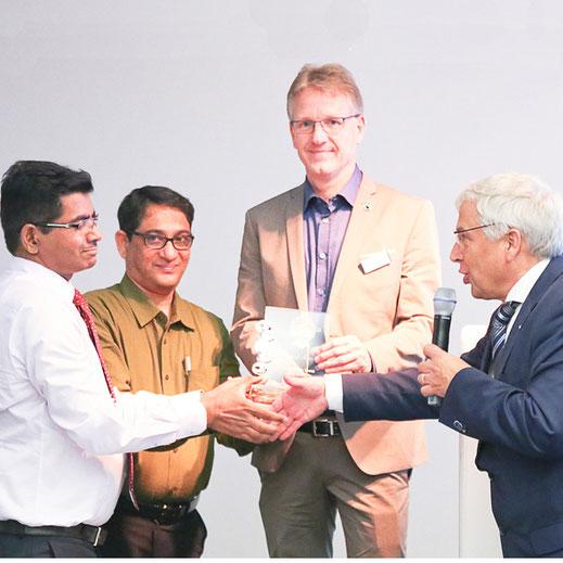 Die Partner des von Dibella ins Leben gerufenen Chetna-Projekts  (Ranga  Rajan,  CEO  Dibella  India,  Arun  Chandra,  President Chetna  Organic  und  Ralf  Hellmann,  CEO  Dibella)  nehmen  die  CINET-Auszeichnung von Peter Wennekes entgegen.