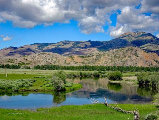 Fluss, grüne Wiesen, Sträucher, Berge, blauer Himmel mit weissen Wolken