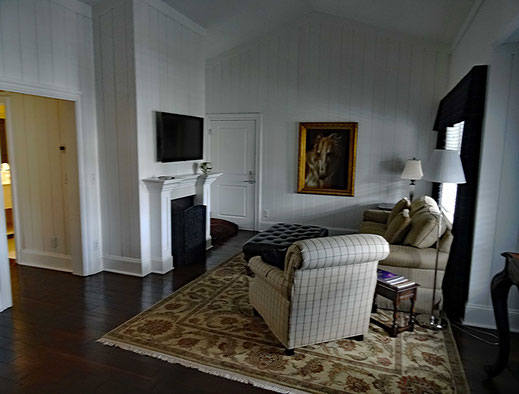 Motoglobe_Motorradreisen. Das Hotelzimmer hat zwei Räume und im einen steht ein weisser grosser Stuhl mit kleine Tisch, Stehlampe und Cheminee.