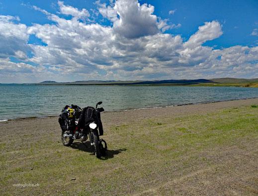 Kiesstrand, See, Motorrad, Gepäck, blauer Himmel mit weissen Wolken