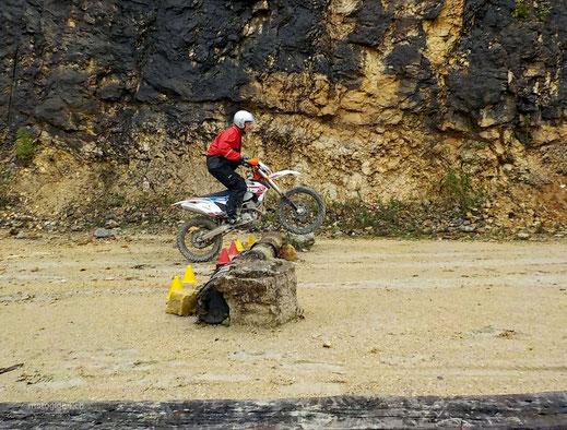 Motoglobe_Motorradreisen. Der Motorradfahrer steht auf dem Motorrad und überquert mit diesem einen Baustamm in einer Kiesgrube.