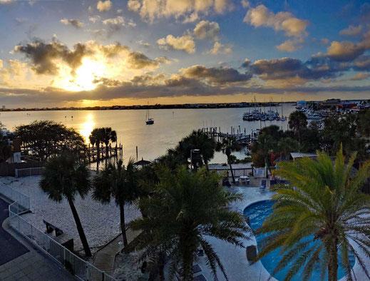 Motoglobe_Motorradreisen.  Die Sonne steht kurz vor dem untergehen hinter ein paar Wolken und der Hotelpool mit seinen diversen Palmen steht vor uns.