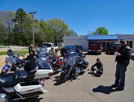 Motoglobe_Motorradreisen. Die Motorräder stehen neben den Tanksäulen und die Fahrer/- innen sitzen am Boden oder stehen und essen etwas.