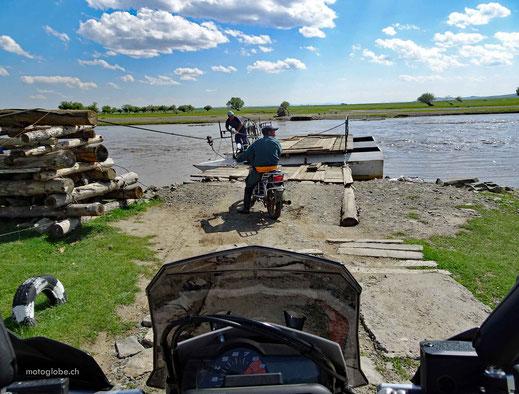 Fluss, Ziehfähre, Motorradfahrer, Baumstämme und grüne Wiese