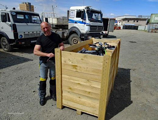 Holzkiste mit einem Motorrad drin, Menscha am schrauben, Kiesplatz, Lastwagen, Haus,