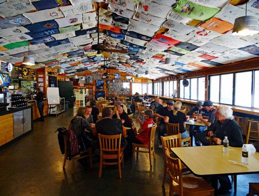 Motoglobe_Motorradreisen. Im Restaurant hat es nebst vielen Tischen und Stühlen ein unmenge von T-Shirts, welche alle an der Decke hangen.