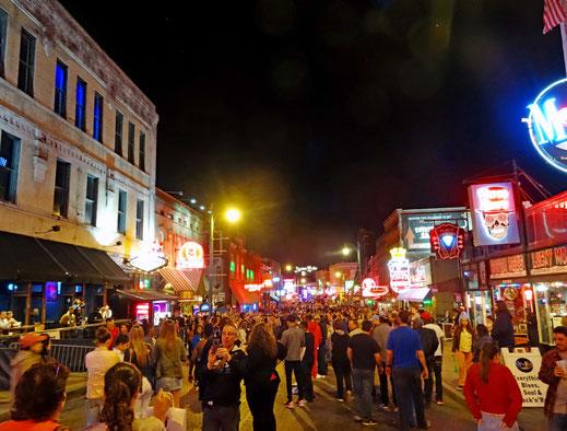 Motoglobe_Motorradreisen. Es ist dunkel und es befinden sich sehr viele Leute auf der Beale Street in Memphis, USA.