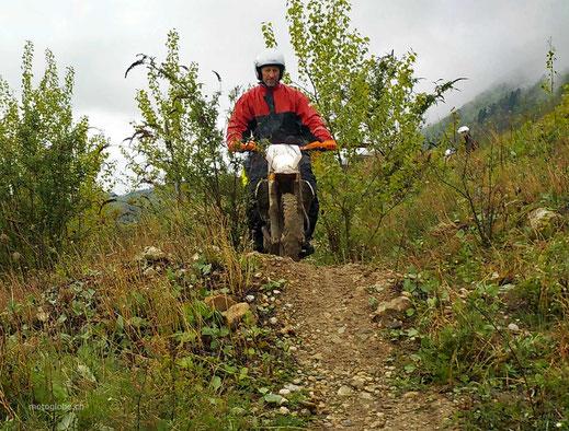 Motoglobe_Motorradreisen. Auf einem schmalen Schotterweg, welche steil abfällt, ist ein Enduromotorrad unterwegs und der Fahrer steht .