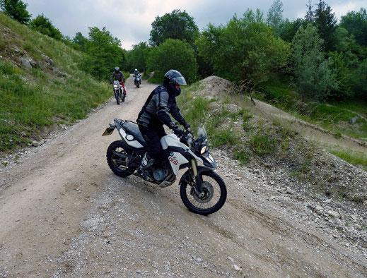 Motorradreisen Motorrad mit Fahrer auf einer Schotterstrasse die steil abfällt