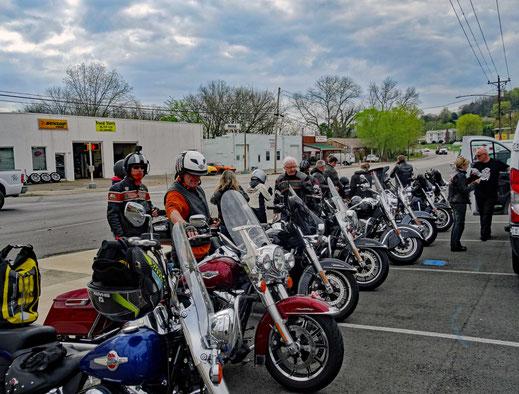 Motoglobe_Motorradreisen. Die Harley Davidson Motorräder stehen auf eine Parkplatz neben dem grossen Bus und die Fahrerinnen und Fahrer stehen rauchend daneben.