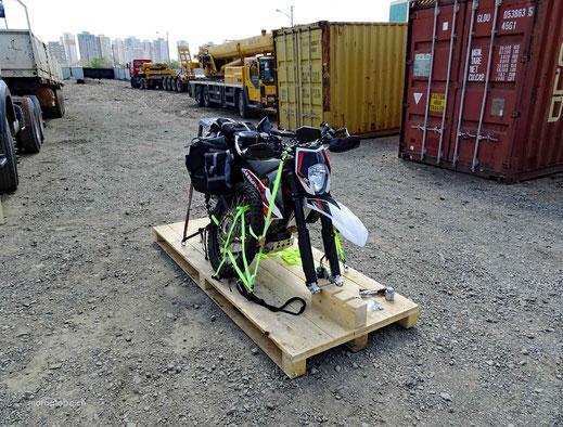 Motorrad auf Verpackungskiste, Festzurrbänder, Container, Lastwagen, Kiesplatz, Hochhäuser