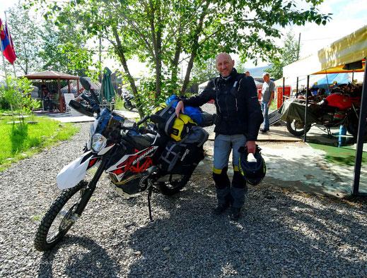 Motorrad, Mensch in Töffkleider, Helm, weitere Motorrader, grüner Baum, Fahne